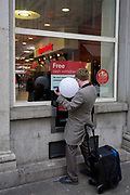 A man carrying a lighting fixture attached to his hand, makes a withdrawal from a bank's cash dispenser, on 22nd November 2017, in London England.