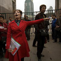 Ms. Wu Ping, in red, and her brother Wu Jian, center right, stand in front of the construction site gate that bars Ms. Wu from her home in the Yang Gong Ping area of Chongqing city on Wednesday 21 March 2007. Ms. Wu has not come to an agreement with the developer who is building on the land and she has been blocked from her home for the past two years.
