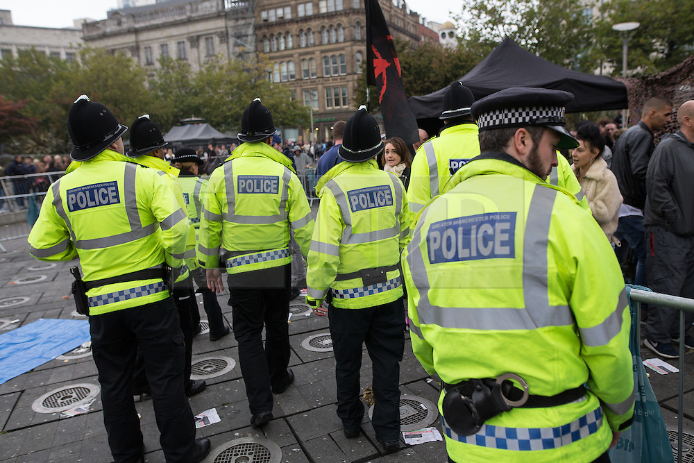 © Licensed to London News Pictures . 03/10/2015 . Manchester , UK . Police move towards the protest site on fountains in Piccadilly Gardens . Protesters against the Conservative government's policies hold a non-stop rave in Piccadilly Gardens in Manchester City Centre ahead of the Conservative Party's annual conference . Photo credit: Joel Goodman/LNP