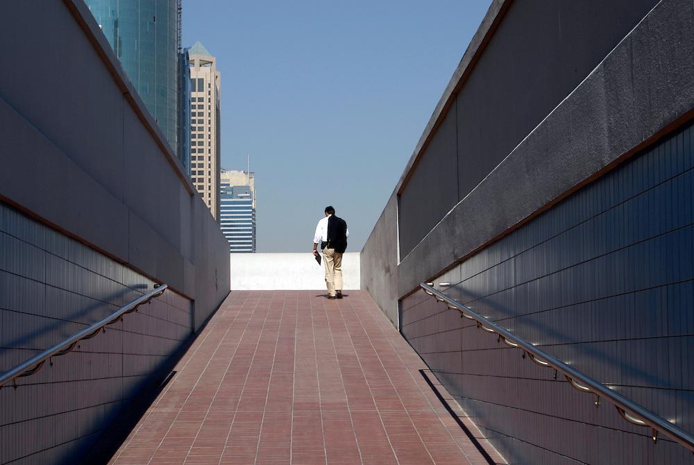 UAE;VAE; Vereinigte Arabische Emirate, Dubai, Ein Mann geht eine Unterführung hinauf in einen business district of the Sheikh Zayed Road    a man is walking alone in the heat of Dubai upwards to a business district of Sheikh Zayed Road   