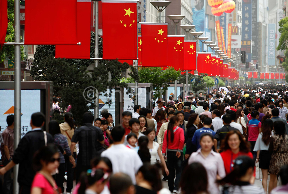 """Pedestrians and tourists crowd onto the Nanjing East Road pedestrian shopping street during on International Labor Day, a public holiday, in Shanghai, China, on  May 01, 2011. The road is one of the most visited sites in Shanghai as it is known as the """"No. 1 Road of China"""" due to its rich history and countless shops and department stores."""