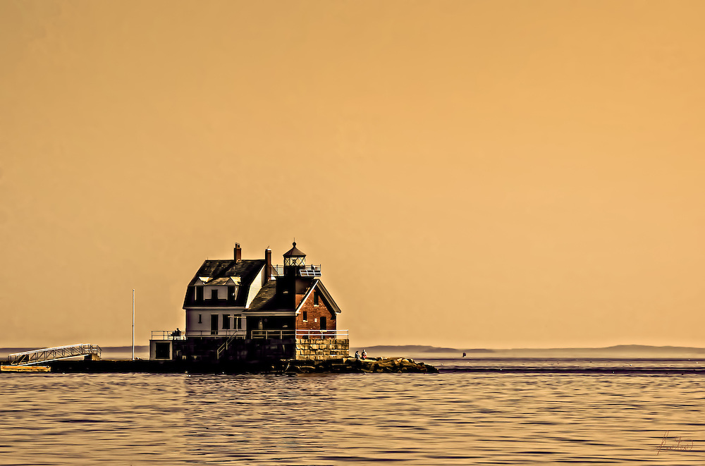 This is a view of the Jameson Point Breakwater Light in Rockland, ME. It was caputred at sunset from a boat in the Harbor. The light is wonderful and the people, on both sides of the building are sitting and enjoying the show.