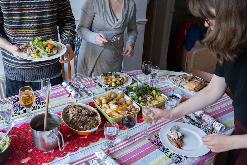 Members of a British family help themselves to a turkey and vegetables Christmas Day lunch, on 25th December 2020 in London, England. Christmas lunch or dinner in the UK is the main meal during the December Christian celebration, when families traditionally come together for the high-protein turkey and high-fibre vegetables - one of the most nutritious meals of the year.