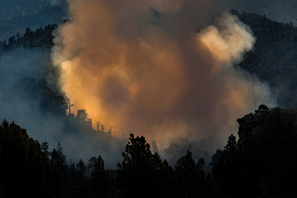 An orange cloud of smoke rises from a forest fire near Barillas, Huehuetenango, Guatemala.