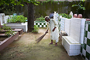 A man sweeps graves in the Qutbuddin Bakhtiar Kaki dargah in Mehrauli, Delhi, India