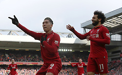 Liverpool's Roberto Firmino (left) celebrates scoring his side's third goal of the game with Liverpool's Mohamed Salah during the Premier League match at Anfield, Liverpool.