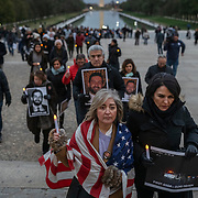 WASHINGTON, DC - NOVEMBER 17: Kelly Ghaisar ascends the steps of the Lincoln Memorial wrapped in her son's American flag and her cousin Behnaz Raissian at her side during a candlelight vigil commemorating the second anniversary of Bijan Ghaisar's death in Washington, DC on November 17, 2019.(Photo by Craig Hudson for The Washington Post)