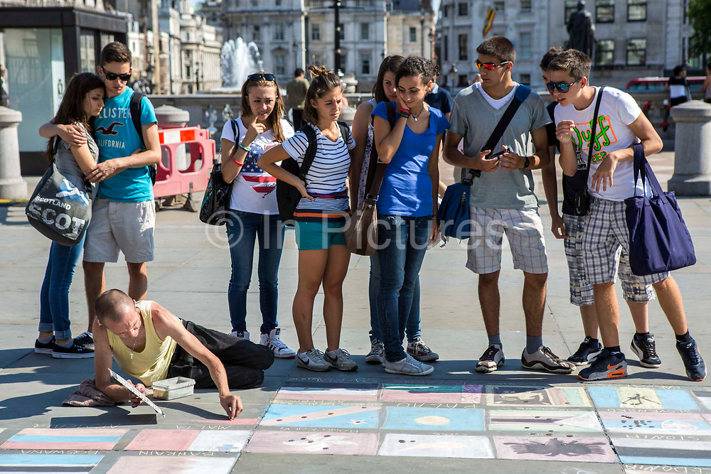 Tourists place money on their country flag, a project by a homeless group to raise money.  Trafalgar Square, London, UK.
