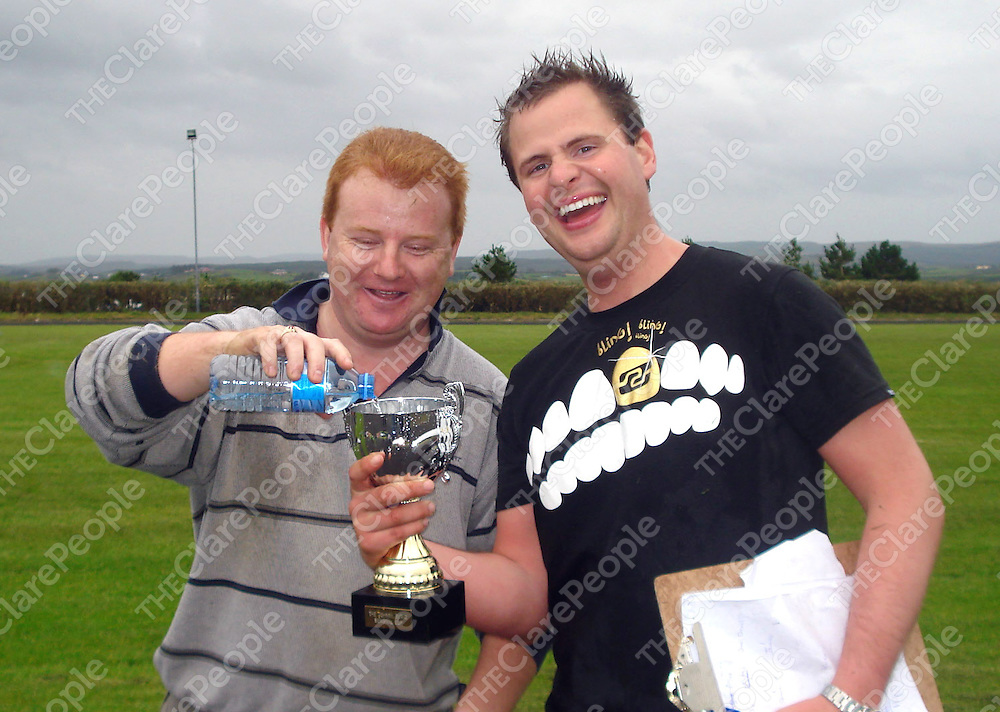To the victor - the spoils: Derek Logue of the Bellbridge Hotelfills the Johnny Burke Memorial Cup for Armada Hotel team captain John Burke after their annual football challenge in Mullagh.