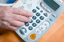 Older person using a large button telephone to make dialling a phone number easier to see when making a phone call,