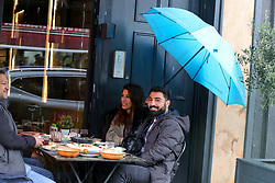 © Licensed to London News Pictures. 02/05/2021. London, UK. People dining outside a restaurant as heavy rain falls  in north London. Windy and wet weather is forecasted for the bank holiday Monday. Photo credit: Dinendra Haria/LNP