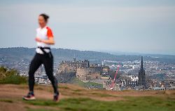 Edinburgh, Scotland, UK. 5 April, 2020. On the second Sunday of the coronavirus lockdown in the UK the public are outside taking their daily exercise. A woman running on Salisbury Crags in Holyrood Park with Edinburgh Castle in distance. Iain Masterton/Alamy Live News