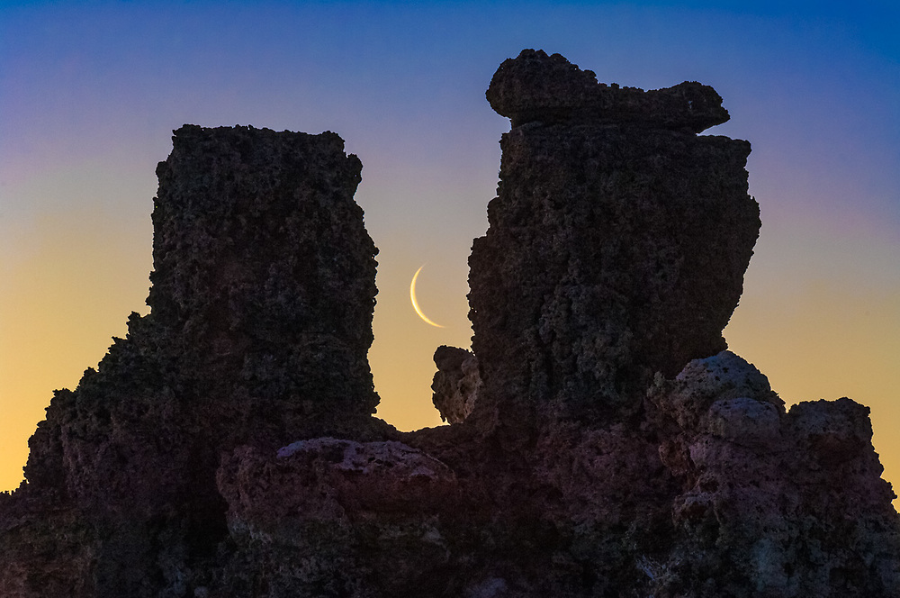 Tufa towers and crescent moon, morning light, April, eastern Sierra Mountains in the distance,  Mono Lake State Natural Reserve, Mono County, California, USA