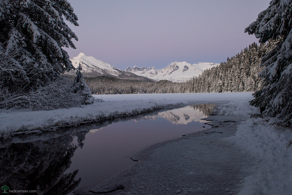 Fresh snow had fallen throughout Juneau earlier in the week and cold weather and clear skies soon followed for a number of days. Taking advantage of these conditions I headed out to photograph around the area. In the middle of winter this is really only about seven hours but with the low light it is easy to take advantage of all that time quite quickly. Stopping by Auke Lake on the way back into the downtown area was more so a chance stop at the right time as some color filled the skies over Mendenhall Glacier in the distance.