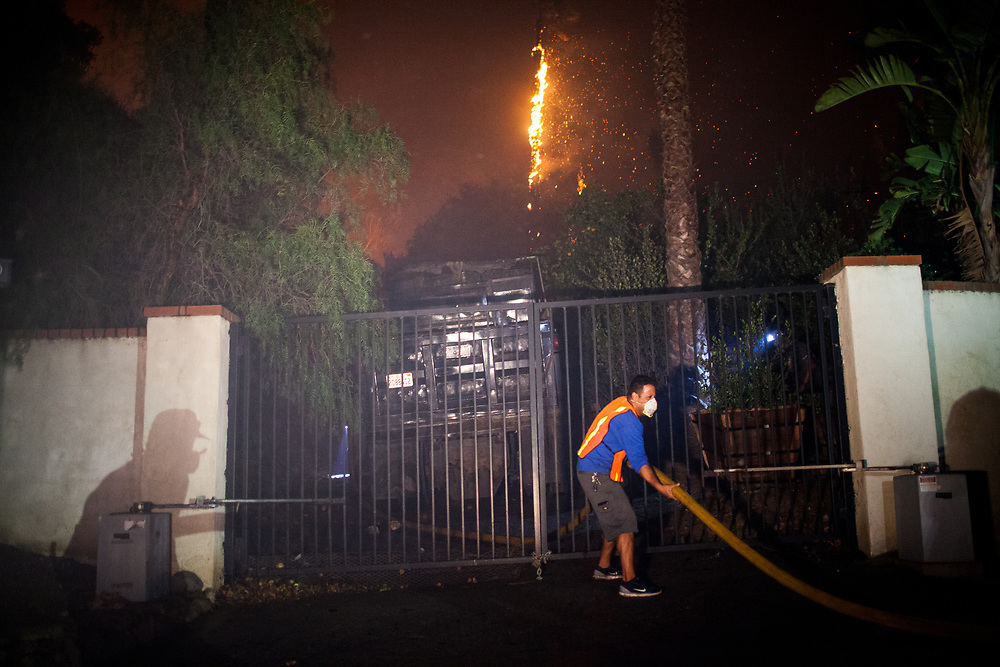 A local resident helps push a water hose through a residential gate to prevent a fire from spreading during the Woolsey Fire in Malibu, California, Friday, November 9, 2018.