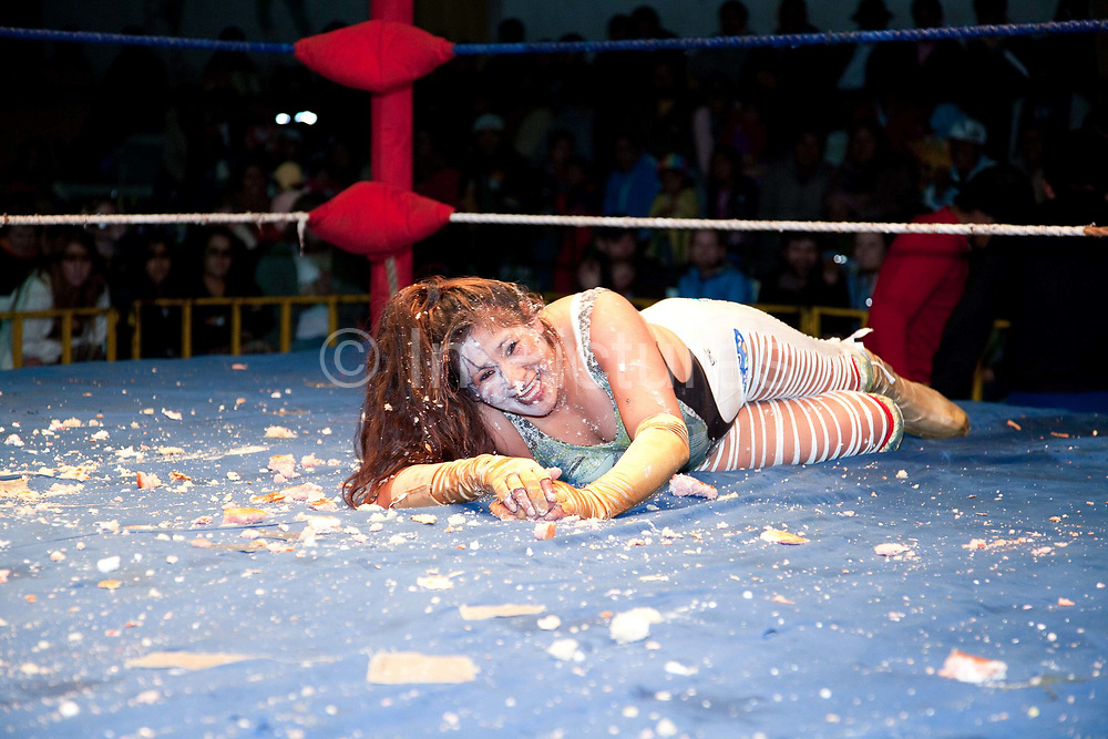 Female wrestler on floor amindst pie cake debris smiling at camera. Lucha Libre wrestling origniated in Mexico, but is popular in other latin Amercian countries, including in La Paz / El Alto, Bolivia. Male and female fighters participate in the theatrical staged fights to an adoring crowd of locals and foreigners alike.