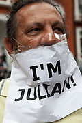 "London, UK. Thursday 16th August 2012. Supporter of Julian Assange outside the Ecuador Embassy with his mouth / voice covered up with a sign saying ""I'm Julian""."