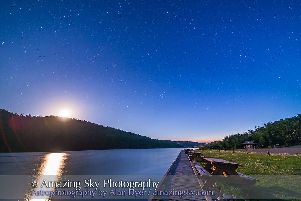 The Big Dipper and Ursa Major (at upper right), Arcturus (left of centre), and the waxing 6-day Moon (overexposed at left) in the deep twilight at Reesor Lake in the Cypress Hills, Alberta, July 29, 2017. The Big Dipper is slightly distorted by the wide-angle lens. <br /> <br /> This is a single 30-second exposure with the Rokinon 14mm SP lens at f/2.5 and Canon 6D at ISO 800.