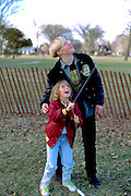 Cousins age 16 and 7 flying kite at Easter family gathering. Victory Memorial Drive Minneapolis Minnesota USA