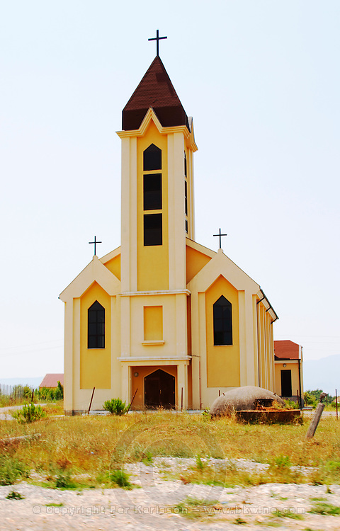 An abandoned church in the countryside. Surrounded by a fence. In font of the church a typical Albanian bunker such as can be seen all over the country side near the border. Yellow and white. Albania, Balkan, Europe.