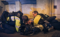 © licensed to London News Pictures. 22/04/2011. Bristol, UK  .  Police attend to an injured person. Hundreds of protesters stormed a controversial Tesco store only days after it opened, causing tens of thousands of pounds worth of damage and injuring eight police officers. It came after police had raided a nearby squat at the centre of a campaign against the supermarket giant. Four people where arrested on suspicion of  plotting a firebomb attack on the new shop. Photo credit should read Jonathan Taphouse/LNP