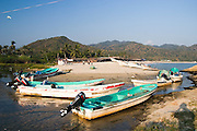 The boats of Pomaro fishermen are lined up on the beach near the village of Maruata, Michoacan State, Mexico. The beautiful bay is a popular destination among independent-minded travelers.