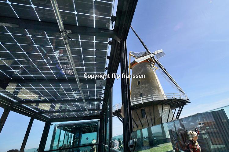 Nederland, Vlissingen, 15-9-2019Vanaf de aanlegsteiger van de pont over de westerschelde in vlissingen rijdt een elektrisch treintje op energie van zonnepanelen naar het centrum van de stad om passagiers en dagjesmensen te vervoeren . Het rijdt ook langs de molen aan de zeedijk . Foto: Flip Franssen