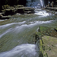 MONTANA. Summer hikers play at Ouzel Falls near Big Sky in the Gallatin Mountains.  Gallatin National Forest.