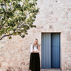 Collette Dinnigan, posing against an outside wall of her villa. Ostuni, Italia. September 28, 2019.