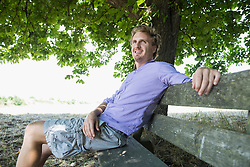 Mid adult man sitting on bench, smiling