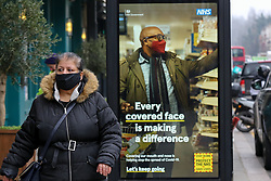 © Licensed to London News Pictures. 02/03/2021. London, UK. A woman wearing a protective face covering walks past the government's 'Every covered face is making a difference' awareness poster in north London. The number of Covid-19 infection rate and deaths have dropped more than a quarter within a week as the effect of lockdown restrictions and vaccine rollout is making an impact. Six cases of the P1 variant have been identified in people who recently returned from Brazil. Photo credit: Dinendra Haria/LNP