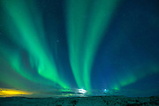 Aurora Borealis spectacular view of the Northern Lights in the sky over snow-covered mountains in glacial landscape, South Iceland