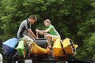 New Windsor, New York - A man and a child tie down kayaks on the roof of their vehicle after kayaking in the Hudson River at the Paddlefest event sponsored by the Mid-Hudson Chapter of the Adirondack Mountain Club at Kowawese Unique Area at Plum Point on June 13, 2010.