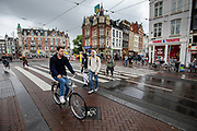 Een man rijdt op de fiets over het Muntplein in Amsterdam.<br /> <br /> A man cycles at the Munt Square in Amsterdam.