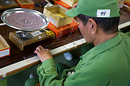 An elderly prisoner sits threading small beads onto string to make beaded fashion accessories, as work undertaken for a client company,  and as part of his daily prison routine, in Onomichi prison, Japan.  Monday, May 19th 2008. The inmates undertake 6 hours a day of light work.