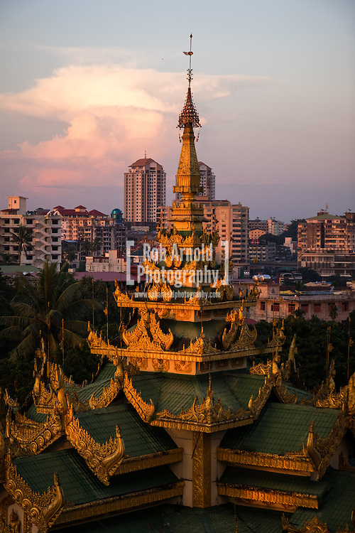 A view of a roof of a temple next to the Shwedagon Pagoda during sunset.