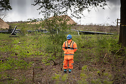 © Licensed to London News Pictures. 28/04/2019. London, UK. A security guard keeps watch near the perimeter fence surrounding High Speed 2 works in the Colne Valley west of London. Extinction Rebellion activists have joined with Stop HS2 protestors to occupy trees in Colne Valley to stop their felling for the HS2 rail project. Workers were expected to start cutting down the trees yesterday and to continue today but the protests have stopped the work. Photo credit: Peter Macdiarmid/LNP
