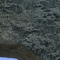 Sam Lightner(MR) rappels on huge Shipton's Arch, one of earth's biggest, in arid Kara Tagh Mountains near Kashgar in Xinjiang, China.