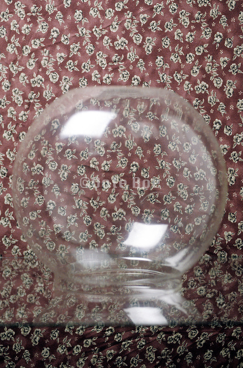 Still life of a glass bowl on a floral print background