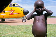 A malnourished child shields his ears from the noise of a Buffalo plane delivering food aid. Ajiep, Bahr el Ghazal, Sudan. The famine in Sudan in 1998 was a humanitarian disaster caused mainly by human rights abuses, as well as drought and the failure of the international community to react to the famine risk with adequate speed. The worst affected area was Bahr El Ghazal in southwestern Sudan. In this region over 70,000 people died during the famine.