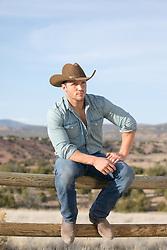 cowboy relaxing on a split rail fence