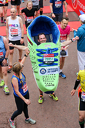 © Licensed to London News Pictures. 28/04/2019. London, UK. A man dressed in a shoe at the finish of 2019 Virgin Money London Marathon. Photo credit: Dinendra Haria/LNP