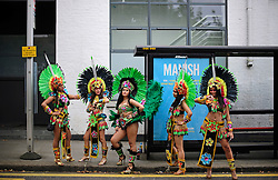 © Licensed to London News Pictures. 29/08/2016. London, UK. Carnival goers in costume wait next to a bus stop before taking part in day two of the Notting Hill carnival, the second largest street festival in the world after the Rio Carnival in Brazil, attracting over 1 million people to the streets of West London.  Photo credit: Ben Cawthra/LNP