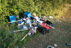 © Licensed to London News Pictures. 28/06/2018. Fetcham, UK.  Dumped rubbish left behind after travellers left Fetcham Recreation ground. The site was occupied by 18 vehicles on Wednesday 27th June and the occupants were issued with a Notice of Direction requesting that they leave by Mole Valley District Council. This has been ignored and the council went to court to seek further legal action yesterday (28th June 2018). Photo credit: London News Pictures