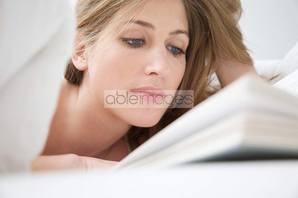 Close up of woman lying in bed reading a book