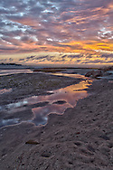 The post-sunset sky reflects in a shallow pool at Paine's Creek Beach in Brewster.