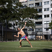 A street performer fine tune his show on the astro turf football court. Lundtoftegade is a housing estate in the heart of Copenhagen. The estate has been on the controversial Ghetto List for years but wastaken off 1st of December 2020. The Ghetto List is based on the Ghetto Law introduced by the Danish Govenrment in 2018. In 2020 a huge campaign was launched to raise 50.000 signatures demanding the Danish Parliament to reconsider the law and to abolish it. Part of the campaign was the national portrait poster campaign 'We ARE the mixed city'. More than 100 local residents in joined the campaign and were photographed in a small make shift studio set up in Lundtoftegade. These images are fragments of life in and around Lundtoftegade 2020.