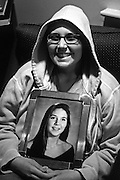 """Always a fan of hooded sweatshirts, Karin became ever fonder of their protective qualities after losing her hair. She holds her high school graduation photo.<br /> <br /> """"Our minds were rarely sad. We strongly believed and often reminded one another that sadness did not fight cancer. Perhaps the best reminder to both of us and to everyone that was affected by the situation, were our frequent displays of silliness, our capacity for normal behavior under abnormal circumstances."""" - Karin Weidenhammer"""