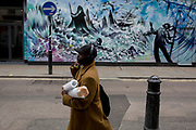 A man listens to music via headphones while carrying some bubble-wrapped tubes, on 3rd March 2020, in London, England.