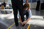 """Security employed by contractor OCS searches a passenger at Heathrow Airport's Terminal 5. Teams of 5-8 perform a rotational order of tasks, changing every 20 minutes: A loader (asking travellers to take off clothing, shoes etc); archway detectors; X-ray operator; liquid tester and bag searcher. The X-ray operator can earn a £50 bonus for a suspect item randomly inserted by undercover officials and known as an Airlock Find. Also, a Tip is a random image flashed on the screen that shows a suspect item they have to spot. A typical day of searched passengers is 25,000 passengers in T5. From writer Alain de Botton's book project """"A Week at the Airport: A Heathrow Diary"""" (2009). ."""